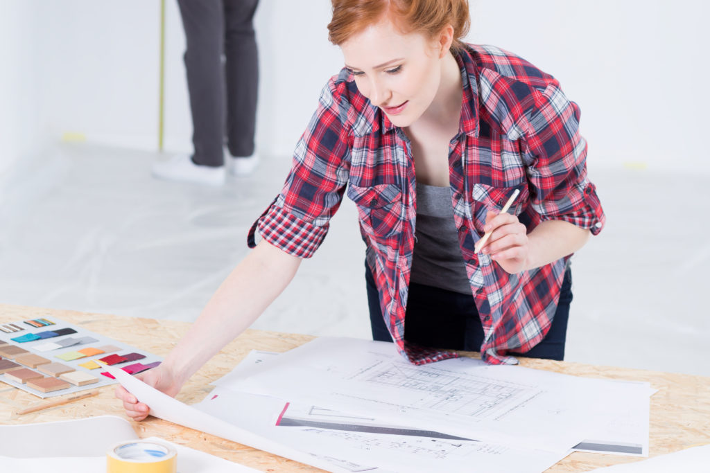Young and red haired woman designer leaning on desk with interior projects and color picker, managing design budget.
